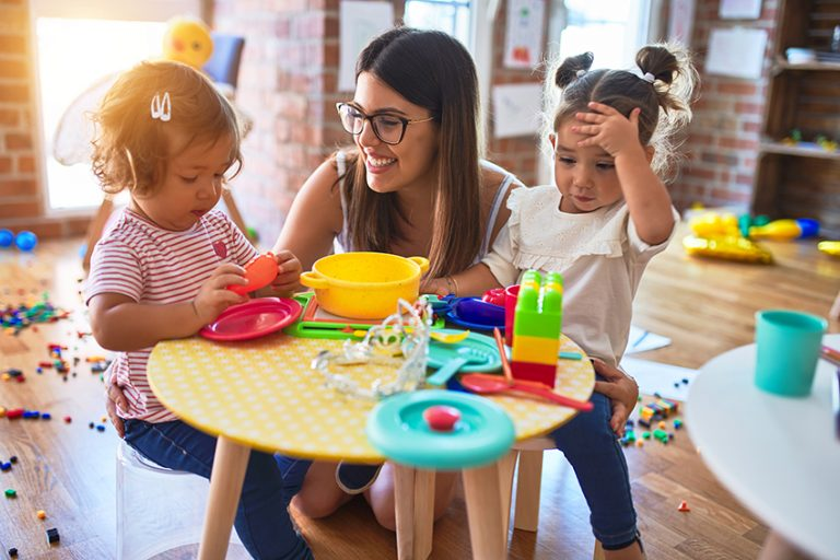 Young teacher and toddlers playing meals using plastic food and cutlery toy at kindergarten